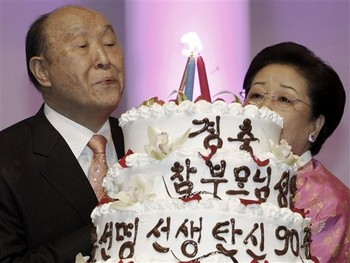 "Rev. Moon Sun-myung, left, founder of the controversial Unification Church, with his wife Han Hak-ja blows out the candles on a cake at his birthday party in Gapyeong, South Korea, Friday, Feb. 19, 2010. Guests from around the world sang, prayed and shouted ""Hurrah"" Friday to celebrate the Rev. Moon's 90th birthday as he is preparing to hand over control of the Unification Church to a Harvard-educated son, Rev. Moon Hyung-jin. The cake reads ""Congratulations! Rev. Moon Sun-myung's 90th birthday."" (AP Photo/Ahn Young-joon) Ah yes: ""Peace and Safety"""
